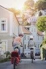 Posterior retrato de familia ciclismo con hija en trailer - foto de stock