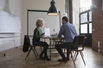 Man and woman discussing paper in boardroom — Stock Photo