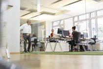Geschäftsmann mit Fahrrad im Gespräch mit Kollege in modernem Büro — Stockfoto