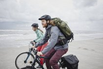 Couple riding bicycles on the beach with cloudy sky on background — Stock Photo