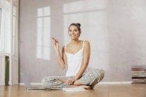 Счастливая молодая женщина сидит на полу с ноутбуком и делает заметки — стоковое фото