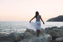 Femme debout sur un rocher en face de la mer au coucher du soleil — Photo de stock