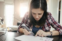 Young woman drawing with 3d pen sitting at table — Stock Photo