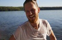 Heureux jeune homme avec un t-shirt mouillé à un lac — Photo de stock