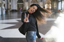 Portrait of exuberant young woman with lollipop in train station showing victory sign — Stock Photo