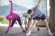 Three athletes doing gymnastics in the city — Stock Photo
