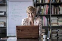 Портрет усміхнений бізнес-леді сидить з ноутбука в сучасний конференц-зал — стокове фото