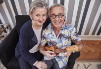 Happy senior couple with man in Hawaiian shirt playing ukulele — Stock Photo