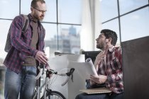 Casual male with bicycle at office desk with male coworker reading magazine — Stock Photo