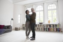 Mature couple standing in living room together — Stock Photo