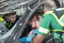 Paramedics helping car crash victim after accident — Stock Photo