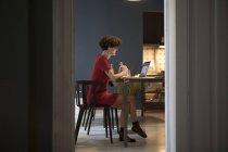 Giovane donna seduta in cucina e utilizzando il computer portatile — Foto stock