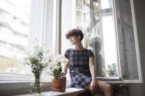 Junge Frau sitzt zu Hause auf Fensterbank — Stockfoto
