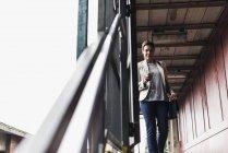 Mature woman using smartphone at train station — Stock Photo
