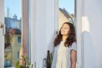 Chica sonriente con los ojos cerrados en la ventana - foto de stock