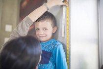 Madre misurazione figlio guardando la fotocamera — Foto stock