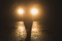 Headlights shining on legs of a woman at night — Stock Photo