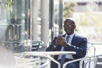 Businessman using cell phone at outdoor cafe — Stock Photo