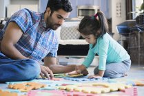 Father and daughter sitting on floor and playing with puzzle — Stock Photo