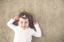 Portrait of little girl lying on the carpet holding funny glasses with plastic nose — Stock Photo