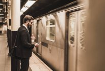 Young businessman waiting at metro station platform, using smartphone — Stock Photo