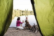 Senior couple camping with dog at a lake — Stock Photo