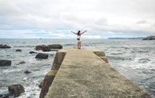 Donna con le braccia distese in piedi sul molo — Foto stock
