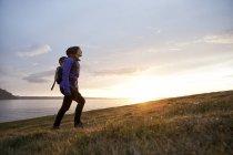 Islândia, mulher caminhando no crepúsculo sobre uma colina — Fotografia de Stock