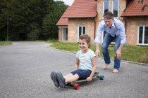 Батько і дочка longboarding в саду — стокове фото