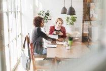 Deux jeunes femmes à l'aide de portable dans un café — Photo de stock
