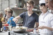 Чоловічий підліток впевнено кухарі з щасливий кухар в кулінарії — стокове фото