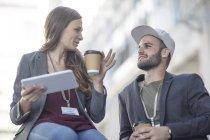 Кейптаун, Южная Африка, два случайных сотрудников на кофе-брейк на цифровой планшет на открытом воздухе — стоковое фото