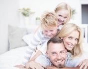 Retrato de la familia sonriente acostada en la cama una encima de la otra - foto de stock