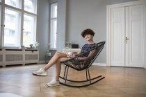 Ritratto di giovane donna sorridente seduta su una sedia a dondolo a casa — Foto stock