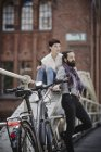 Daytime view of bicycle parked near couple resting on bridge — Stock Photo