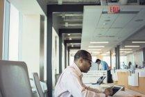 Підприємець, що працюють в офіс з цифровий планшет з колегою на фоні — стокове фото