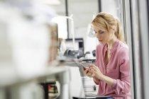 Frau mit Handy im Büro — Stockfoto