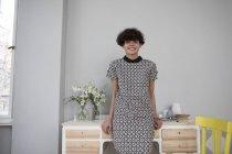 Sorridente giovane donna alla moda in piedi a casa — Foto stock