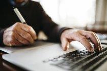Imagen recortada de fotógrafo senior, trabajando con su ordenador en casa - foto de stock