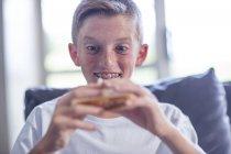 Крупним планом молодий хлопчик тримає в руці сендвіч — стокове фото