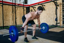 Caucasian sporty man lifting barbell in gym — Stock Photo