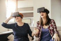 Mère et fille à lunettes de réalité virtuelle, assis sur le canapé — Photo de stock