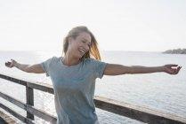 Giovane donna felice sul pontile con retroilluminazione — Foto stock