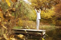 Man standing on a jetty at a pond in autumn — Stock Photo