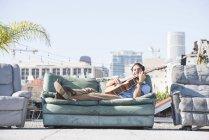 Mann spielt Gitarre sitzend auf Couch auf dem Dach, los angeles, USA — Stockfoto