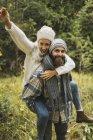 Felice giovane uomo che dà a cavalluccio all'aria aperta in autunno — Foto stock