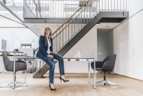 Mujer de negocios con el pelo largo gris sentado en el escritorio en la oficina - foto de stock