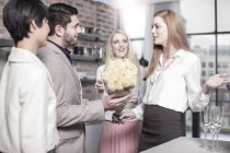 Man handing over roses to woman in kitchen — Stock Photo