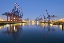 Hamburg city harbor with cranes illuminated in the dusk, Germany — Stock Photo