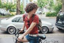 Jovem de equitação da bicicleta na calçada e virando — Fotografia de Stock